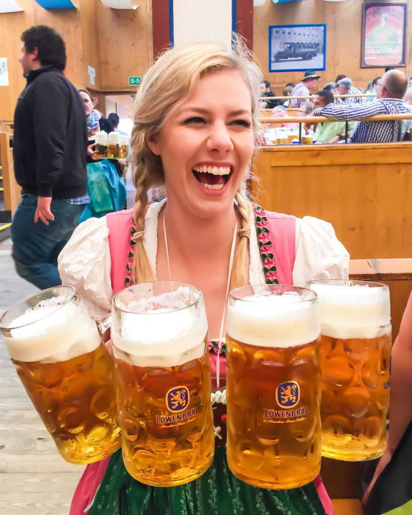 how to be happy; girl at Oktoberfest holding 4 pints of beer